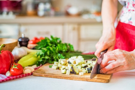 Photo pour Female hand with knife cuts eggplant on board in kitchen. Cooking vegetables - image libre de droit
