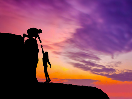Photo pour Silhouettes of two people climbing on mountain and helping. - image libre de droit