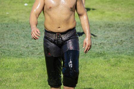 Photo pour oily wrestling, wrestler on green grass - image libre de droit