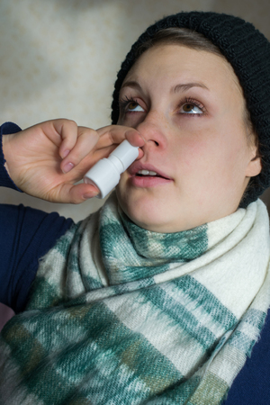 Girl sprays the spray from runny nose into the nasal pass