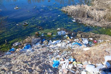 Foto de Garbage thrown to the bank of the river, the topic of environmental pollution - Imagen libre de derechos