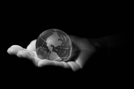 Foto de Glass transparent globe, planet Earth, in the hands of a woman, black and white photo. - Imagen libre de derechos
