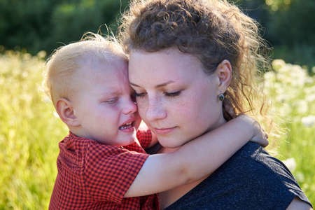 Photo pour Young mom hugs her crying two years old son. - image libre de droit