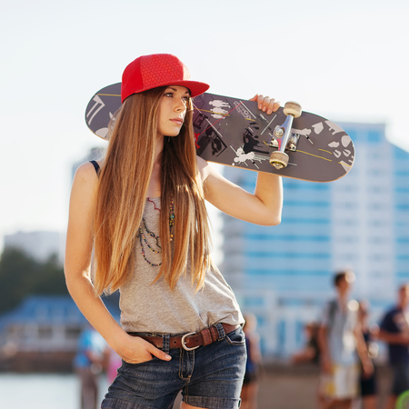 Photo pour Portrait of a girl with a skateboard in her hand, outdoors - image libre de droit