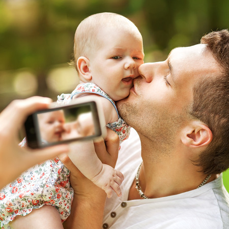 Family with baby In Park taking selfie by mobile phoneの写真素材