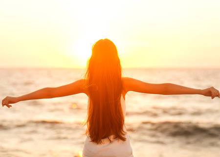 Free woman enjoying freedom feeling happy at beach at sunset. Beautiful serene relaxing woman in pure happiness and elated enjoyment with arms raised outstretched up.