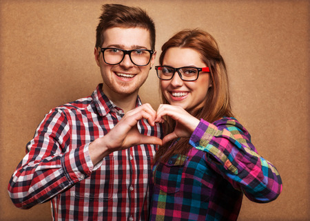 Photo pour Young couple in love make a heart gesture - image libre de droit