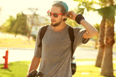 Foto de Hipster style guy. Fashion man on street palm at sunset - Imagen libre de derechos