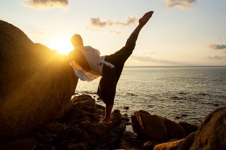 Photo pour guy doing yoga at sunset by the sea - image libre de droit
