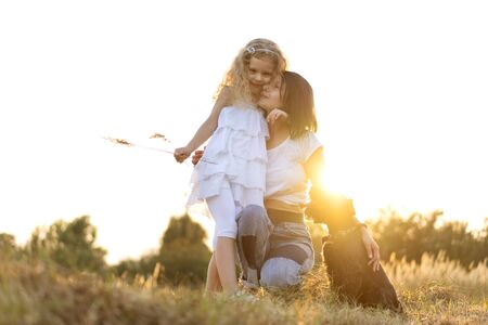 Photo pour Mother with daughter with dog Miniature Schnauzer plays at sunset - image libre de droit