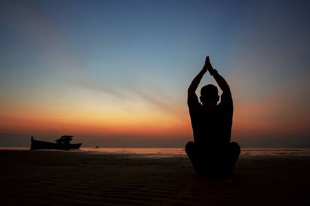 Photo pour guy at sunset on the island practices yoga, silhouette - image libre de droit