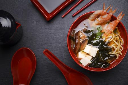 Photo pour Japanese miso soup in a red bowl on the table. - image libre de droit