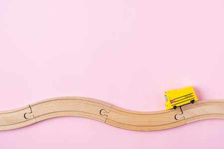 Flat lay back to school composition with yellow school bus model and wooden road on pink background. Transport for students with space for text.