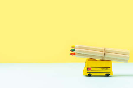 Back to school composition with yellow school bus model and wooden color pencils on pink background. Transport for students. With space for text