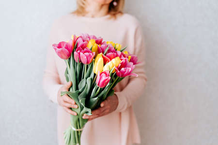 Photo pour Portrait of cropped woman with blonde hair hiding her face, and holding bouquet of pink and yellow tulip flowers. White background, copy space, close up. - image libre de droit