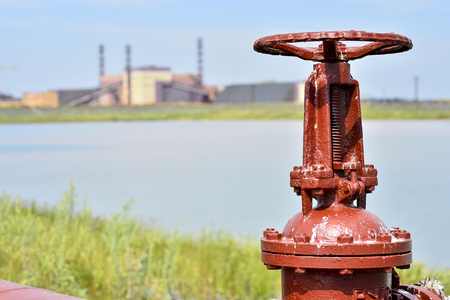 The valve from the pipeline against the background of the factory and an artificial lake