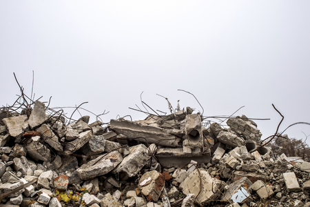 Foto de The rebar sticking up from piles of brick rubble, stone and concrete rubble against the sky in a haze. Remains of the destroyed building. Copy space. - Imagen libre de derechos