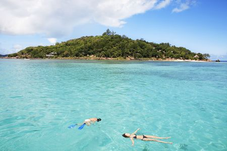 Photo pour tourists snorkling resting in the sea at large of a seychelles island - image libre de droit