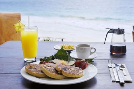 Photo pour continental breakfast composed of pancakes on a plate with coffee maple syrup and orange fruit juice on a wood made table with the beach and the sea on the background - image libre de droit