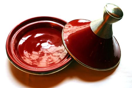 Photo for tajine dish is a special pot for preparing moroccan tajine.The traditional tajine pot is formed entirely of a heavy clay which is sometimes painted or glazed. It consists of two parts; a bottom which is flat and circular with low sides, and a large cone o - Royalty Free Image