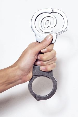 Photo pour hand holding a handcuffs surrending a arobase e-mail sign - image libre de droit