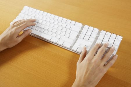 Photo pour hand typing on a wireless white keyboard computer posed on atable - image libre de droit
