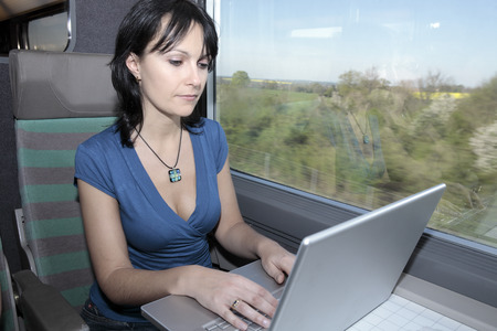 beautiful young woman woman in a train using a computer lap top