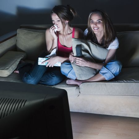 pictures in a living room of two young girls crying sitting on a couch  watching on tv  a sad movie