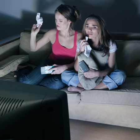 pictures in a living room of two young girls crying sitting on a couch  watching on tv  a sad movi