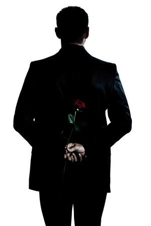 Photo pour one caucasian backside man holding a rose flower portrait silhouette in studio isolated white background - image libre de droit