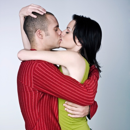 one young couple hugging kissing on studio isolated gray background