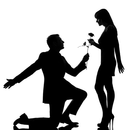 Photo pour one caucasian lovers couple man kneeling offering rose flower and woman in studio silhouette isolated on white background - image libre de droit