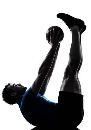 Foto de one caucasian man exercising workout holding fitness ball posture in silhouette studio  isolated on white background - Imagen libre de derechos