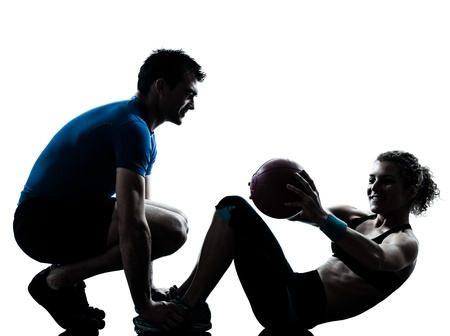 Foto de one caucasian couple man woman personal trainer coach exercising weights fitness ball silhouette studio isolated on white background - Imagen libre de derechos