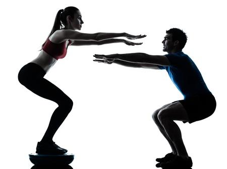 Foto de personal trainer man coach and woman exercising squats on bosu silhouette  studio isolated on white background - Imagen libre de derechos
