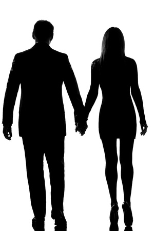 rear view one lovers caucasian couple man and woman walking hand in hand in studio silhouette isolated on white backgroundの写真素材