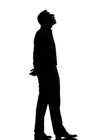 one caucasian business man looking up mouth open  silhouette Full length in studio isolated on white backgroundの写真素材