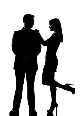 one caucasian couple man and woman standing face to face smiling in studio silhouette isolated on white background
