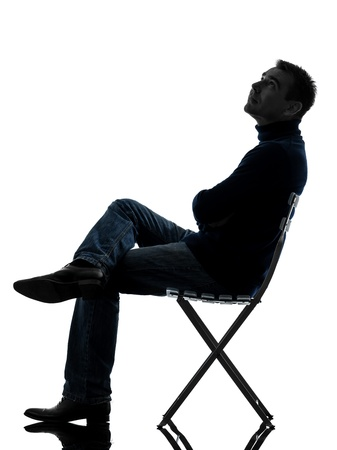 Photo for one caucasian man sitting looking up   full length in silhouette studio isolated on white background - Royalty Free Image