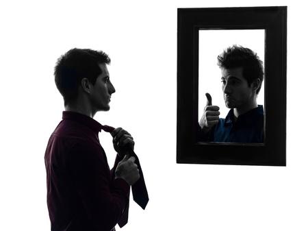 Foto de man in front of his mirror  man in front of his mirror  in shadow  white background - Imagen libre de derechos