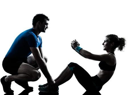 Foto de one caucasian couple man woman personal trainer coach exercising abdominal silhouette studio isolated on white background - Imagen libre de derechos