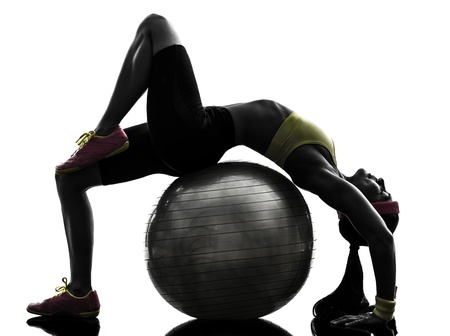 Foto de one  supple woman exercising fitness workout on fitness ball in silhouette  on white background - Imagen libre de derechos