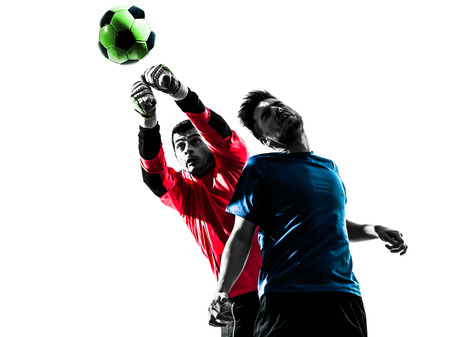 two caucasian soccer player goalkeeper men punching heading ball competition in silhouette isolated white background