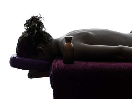 one woman lying on a massage table in silhouette studio on white background