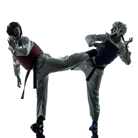 one couple man woman couple exercising karate taekwondo martial arts in silhouette studio isolated on white background