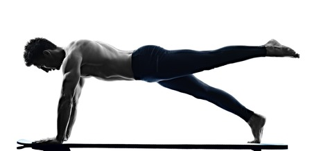 one caucasian man exercising pilates exercises fitness in silhouette isolated on white backgound