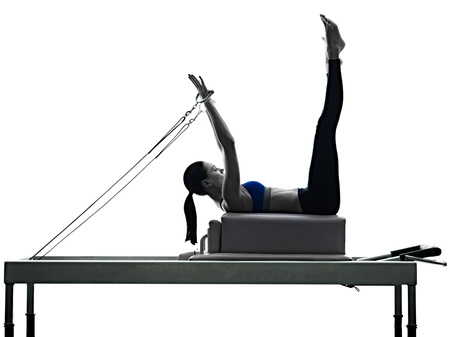 Foto de one caucasian woman exercising pilates reformer exercises fitness in silhouette isolated on white backgound - Imagen libre de derechos