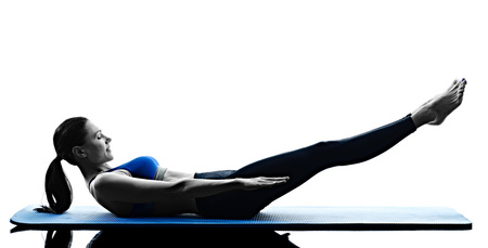 one caucasian woman exercising pilates exercises fitness in silhouette isolated on white backgound