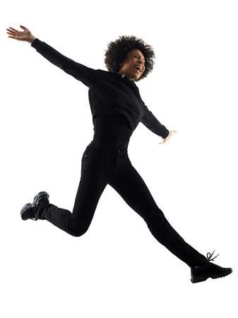 Photo pour one mixed race african young teenager girl woman jumping happy in studio shadow silhouette isolated on white background - image libre de droit