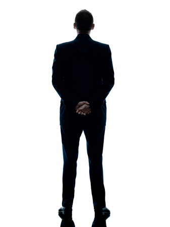Photo for one caucasian business man standing rear view silhouette isolated on white background - Royalty Free Image